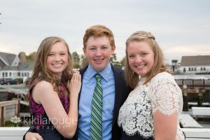 Abigail poses with her two siblings on a pier