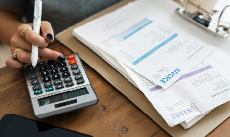 person reviewing invoices with a calculator