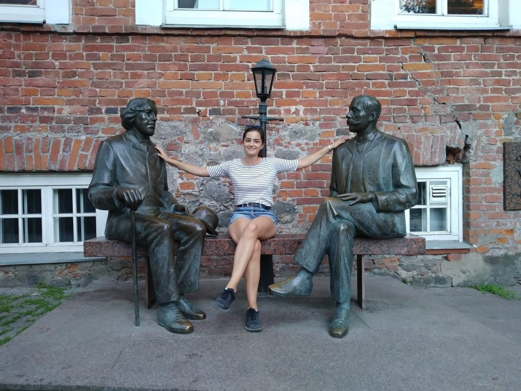 Caroline posing with statues on a bench