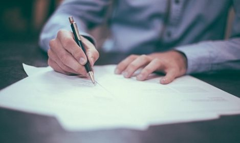 hands with pen, signing documents