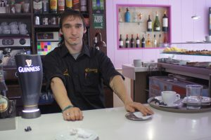 a young male barista at his counter