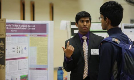 Sujay speaking with a student at a poster presentation