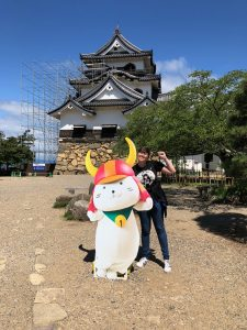 Sydney in Japan posing with large mascot character