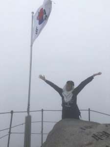 Nabila with her hands in the air, in a fog