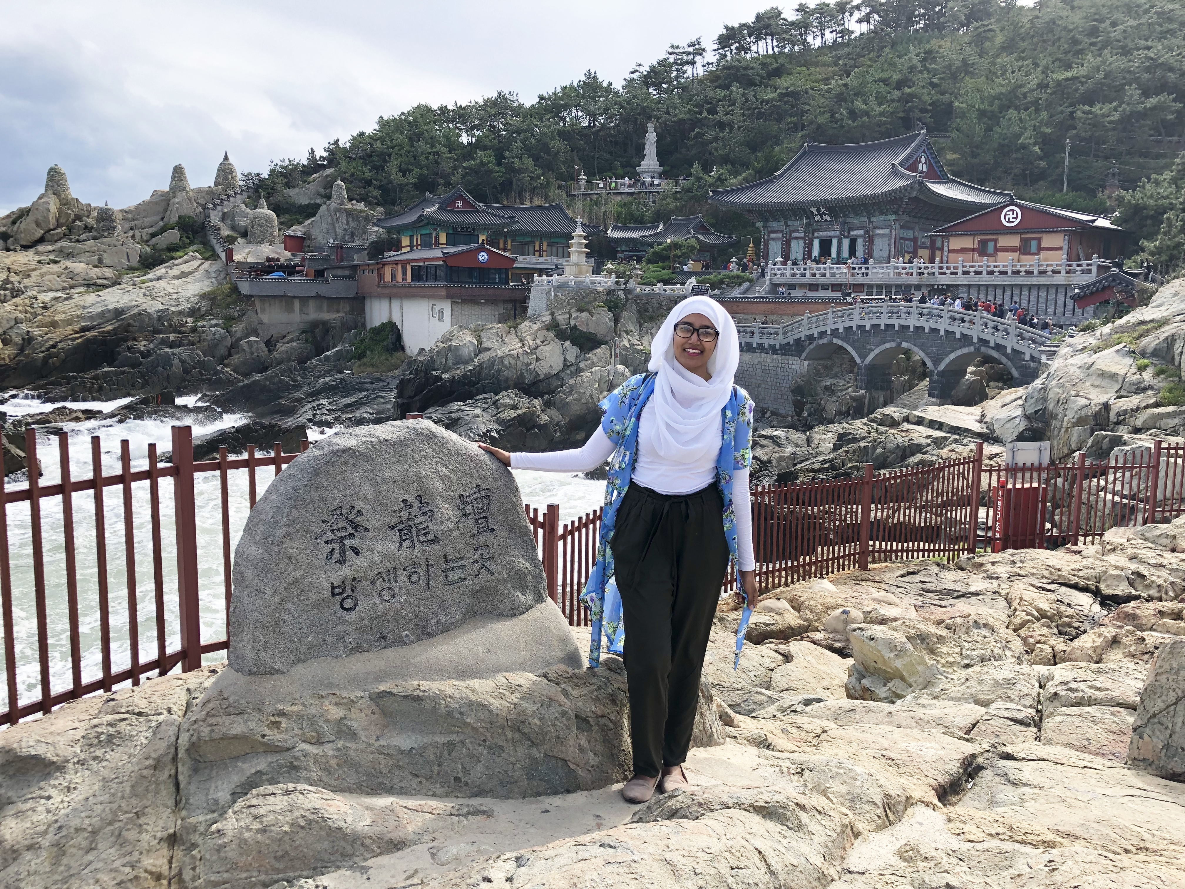 Nabila standing beside a stone with writing in another language