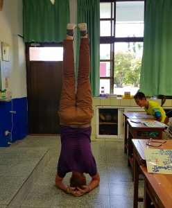 John doing a headstand in a classroom