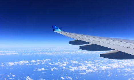 tip of airplane wing with clouds