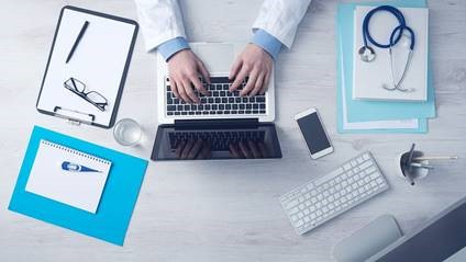 doctor's hands typing at a laptop