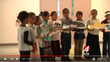 Navajo children holding art with their language on it in a classroom