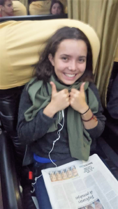 Nina smiling on a bus with a Spanish newspaper