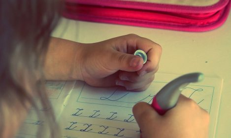 child practicing writing in cursive in workbook