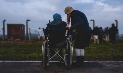 young woman helping someone in a wheel chair