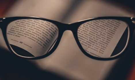 glasses held above a book with text in and out of focus