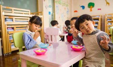 three Asian children eating at a preschool table