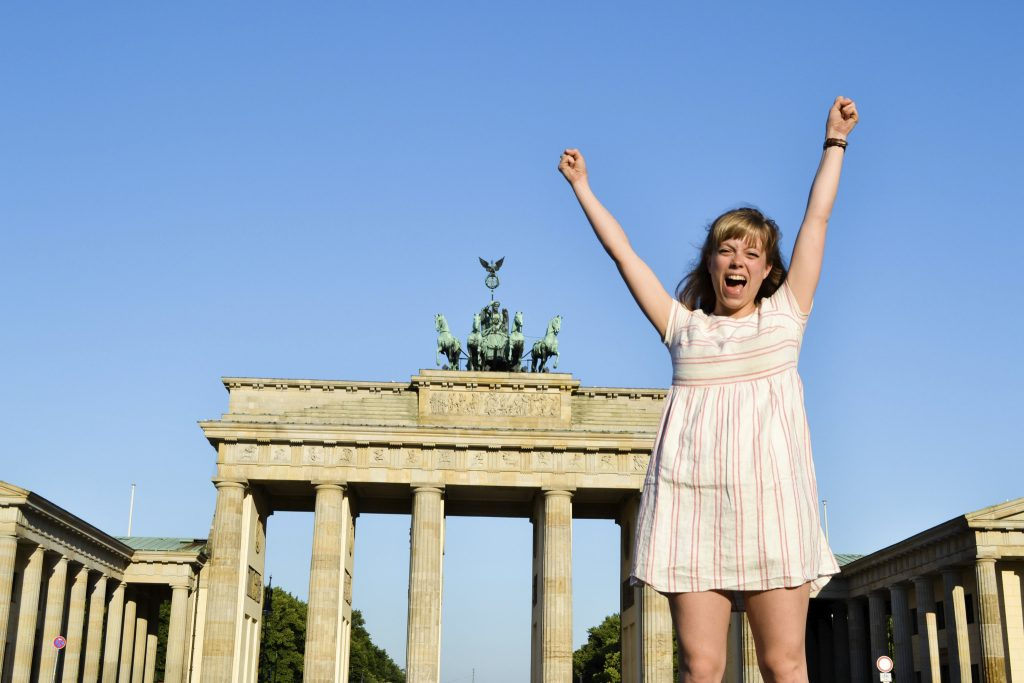 Kate, cheering and arms raised, in Berlin with architecture behind