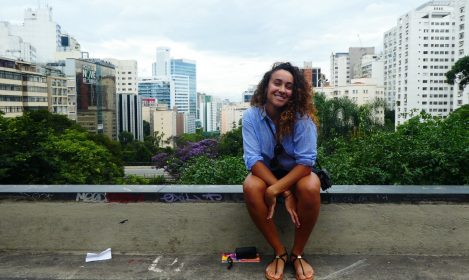 jacinta sitting on a wall with cityscape behind her