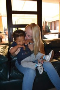 Nicole with a laughing toddler on her lap