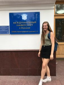 Sydnee with sign on building in Russian
